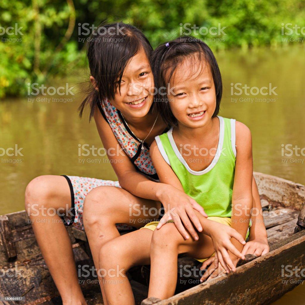 Two Vietnamese girls on boat in Mekong River Delta, Vietnam stock photo