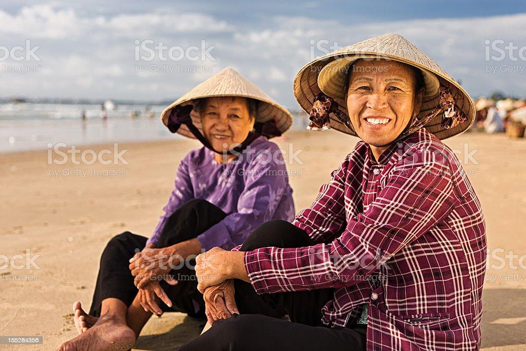 Two Vietnamese women sitting on the beach royalty-free stock photo