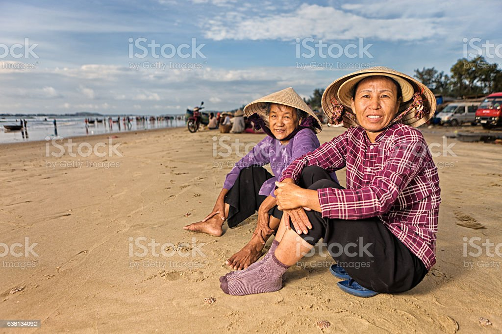 Two Vietnamese women sitting on the beach stock photo