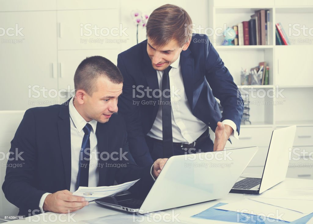 two vigorous men coworkers working on computers in firm office stock photo