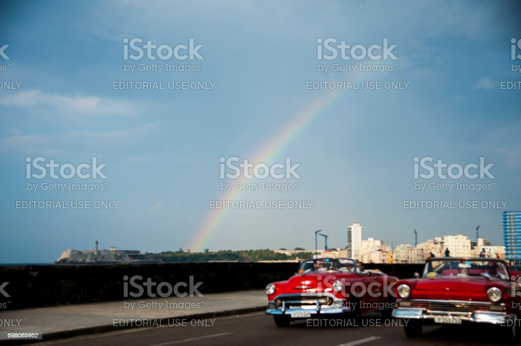 Two vintage cars drive along Havana, Cuba's Malecon with rainbow in background stock photo