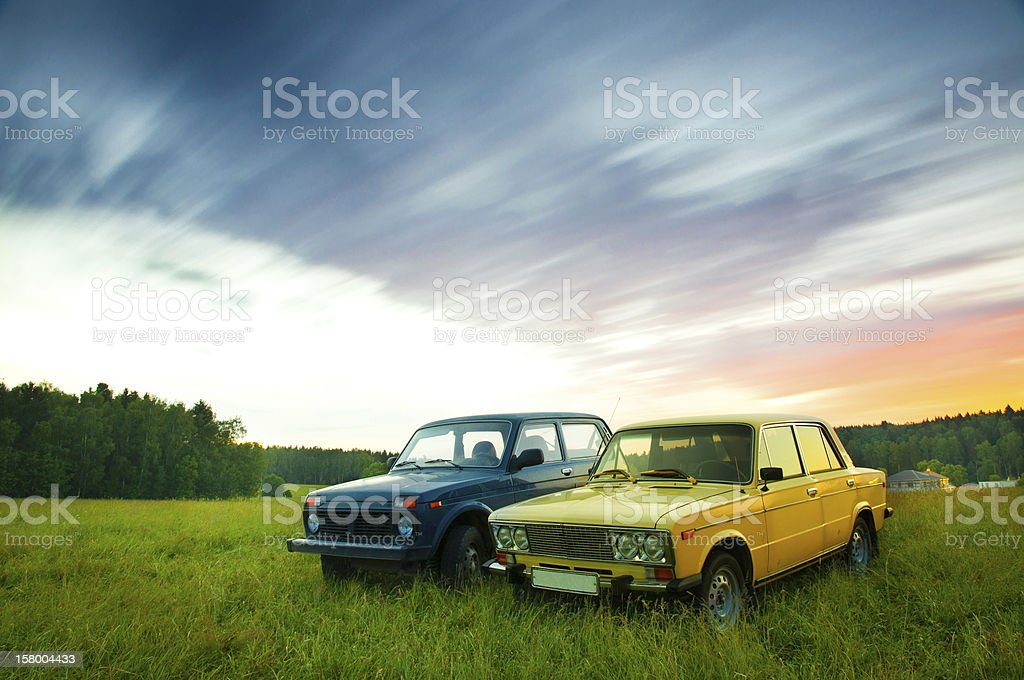 Two vintage cars on a field of green grass at sunset stock photo