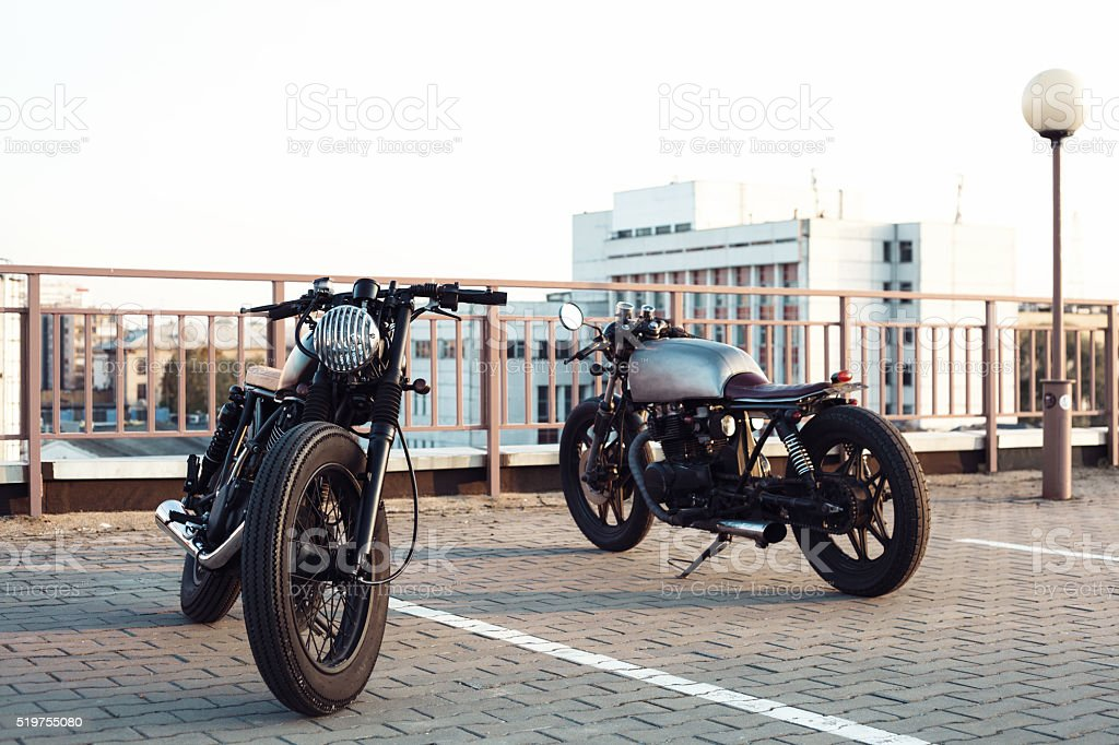 Two vintage motorcycle in parking lot during sunset stock photo