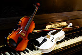 Two violins on a piano