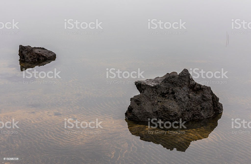 Two Volcanic Rocks and Sand Patterns in Water stock photo
