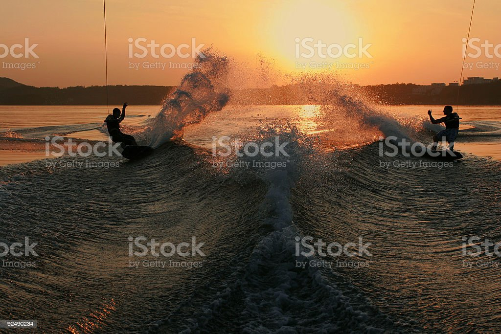 Two wakeboarders slash the wake at sunset stock photo