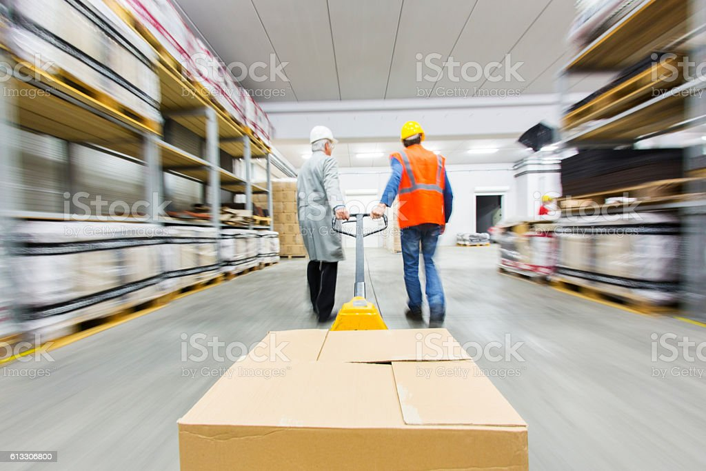 Two warehouse workers pulling pallet truck with boxes.....blurred motion stock photo