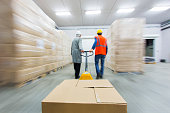 Two warehouse workers pulling pallet truck with boxes.....blurred motion