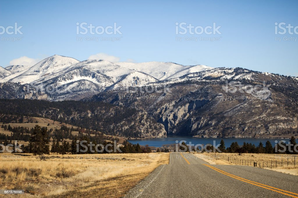 two way road into rocky mountains in the day stock photo