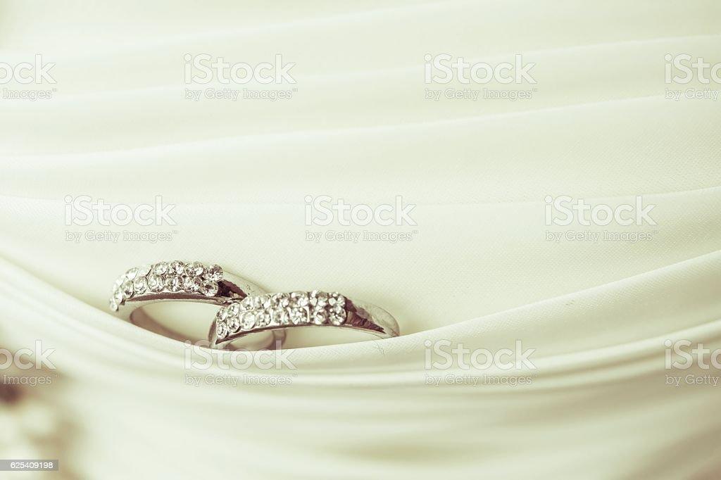 Two wedding rings laying on wedding dress stock photo