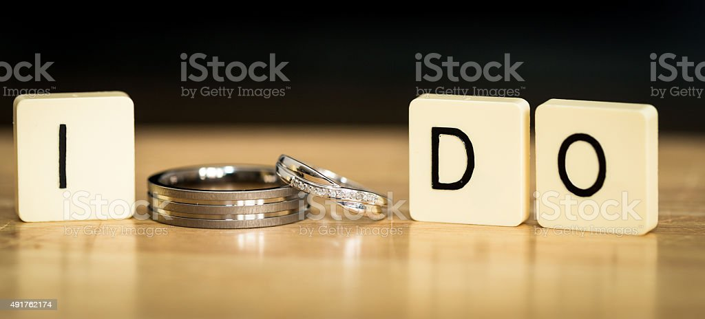 Two Wedding Rings Next to tiles Spelling out 'I do' stock photo