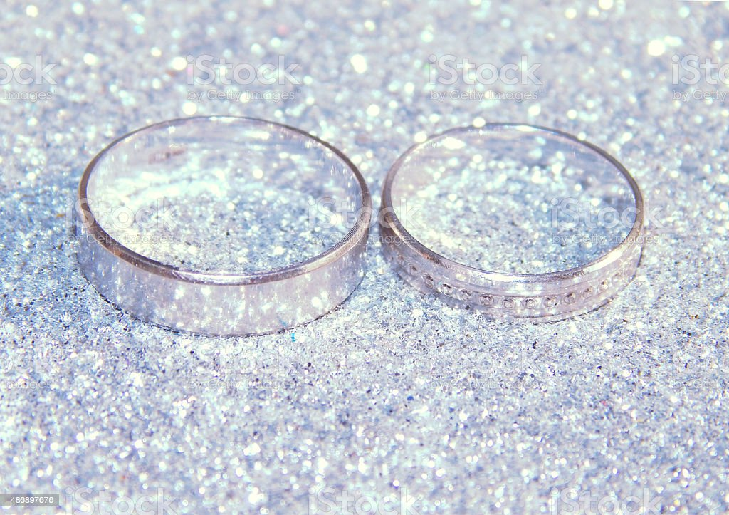 Two wedding rings of white gold on silver glitter sparkle stock photo