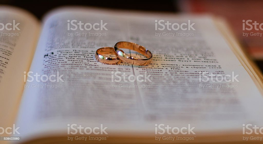 Two wedding rings on a bible stock photo