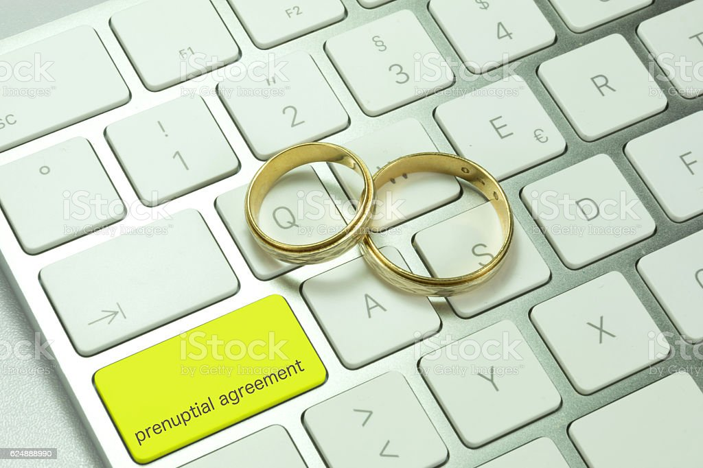 Two wedding rings on a computer keyboard stock photo