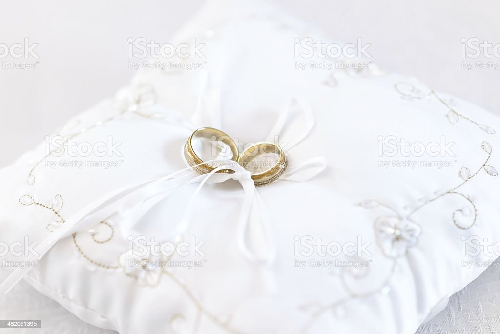Two wedding rings on embroided white cushion. stock photo