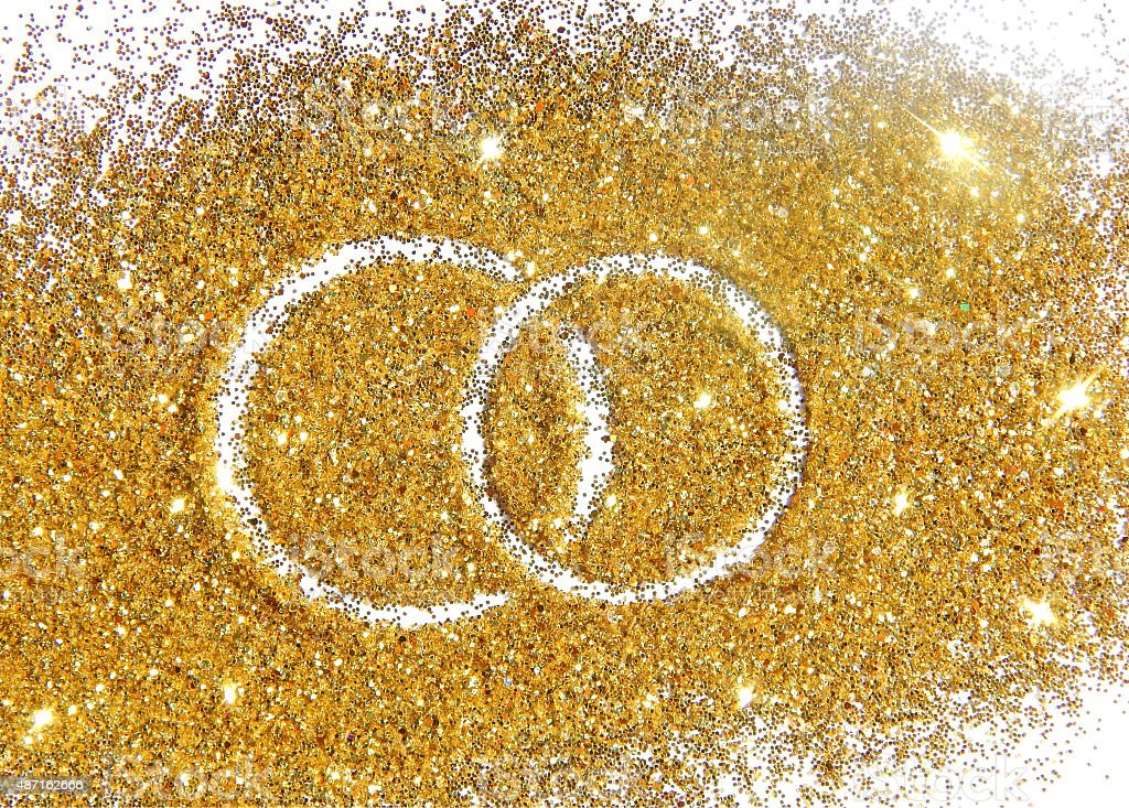 Two wedding rings on gold glitter sparkle on white background stock photo