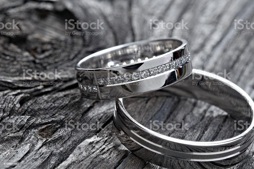 Two wedding rings on rustic wood, b&w stock photo