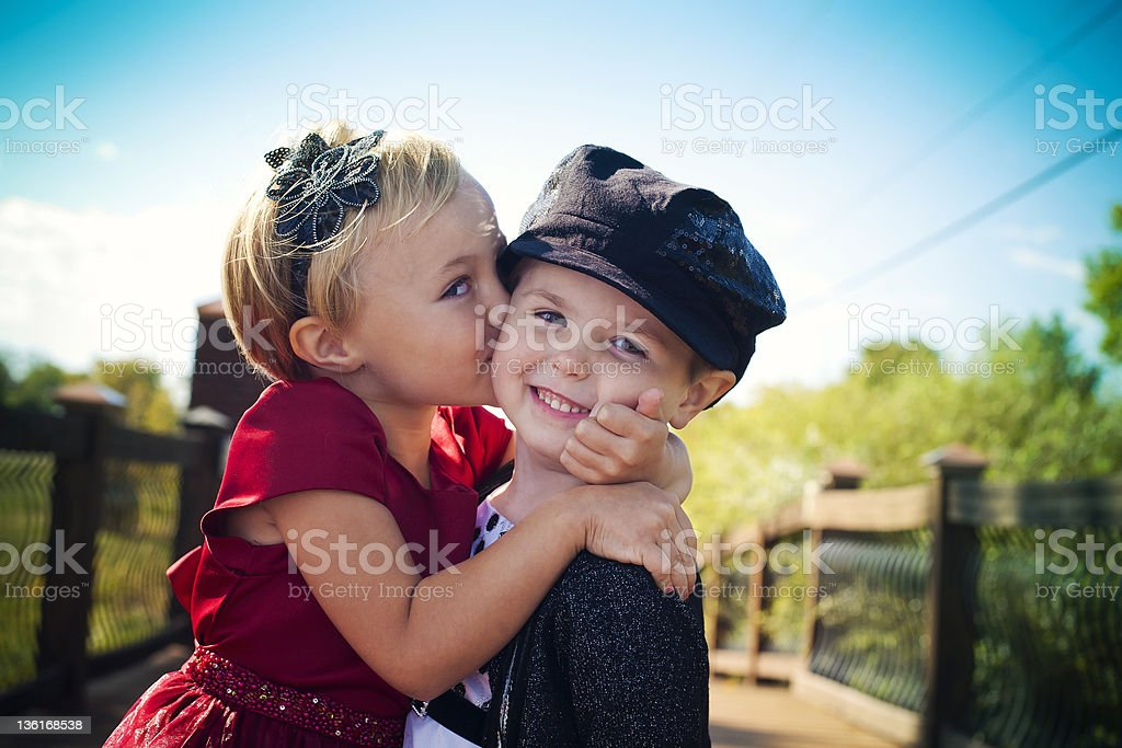 Two well-dressed toddlers embracing and smiling on a bridge stock photo
