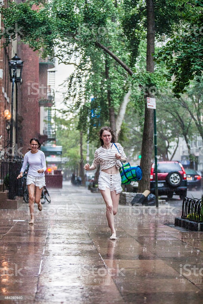 Two wet teenager girl, sisters, running under the summer rain stock photo