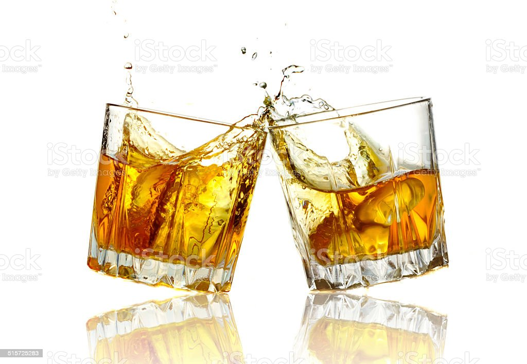 two whiskey glasses clinking together isolated stock photo
