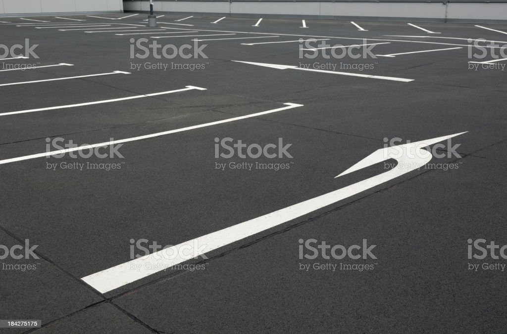 Two white arrows on an empty parking lot royalty-free stock photo
