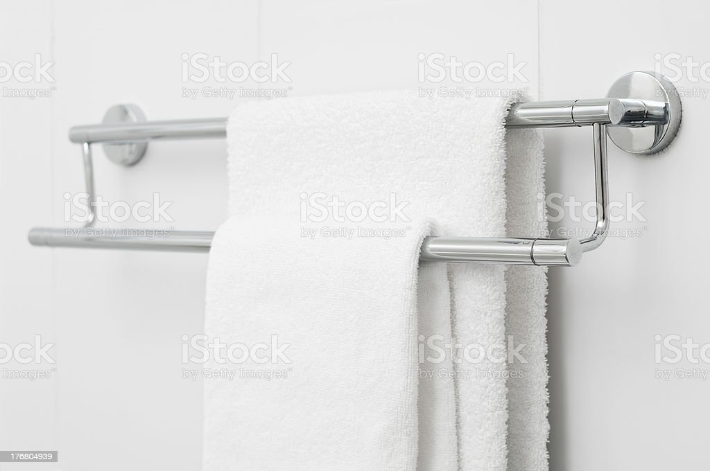 Two white bath towels hanging on tile wall royalty-free stock photo