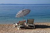 Two white beach chairs and sun umbrella near Adriatic sea