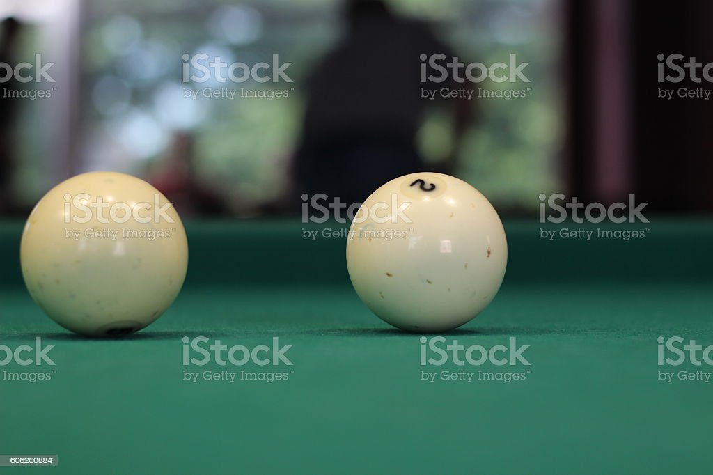 Two white billiard balls on a green billiard table stock photo
