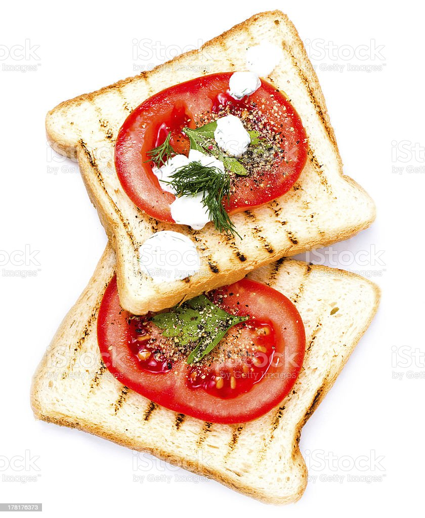 Two white bread toast with tomato, cream, herbs and pepper. royalty-free stock photo