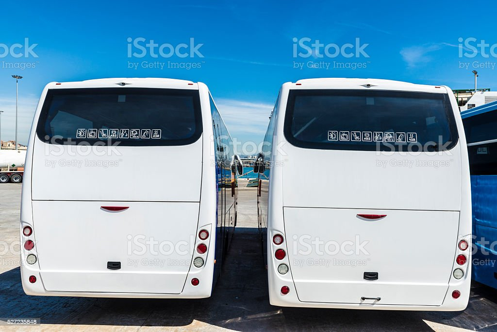 Two white buses parked at the port stock photo