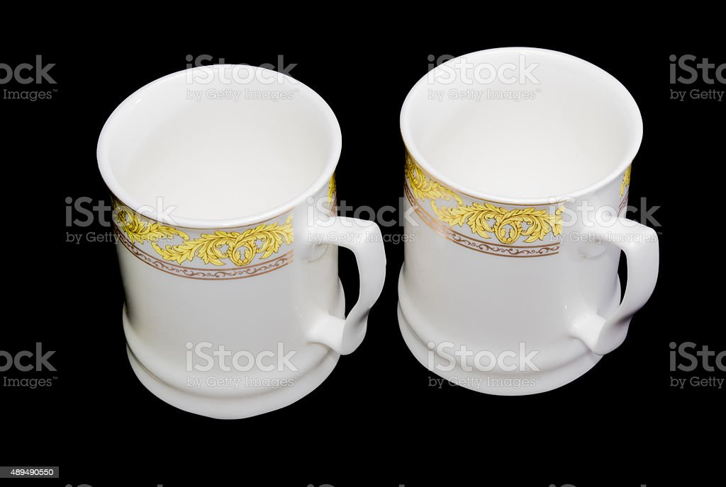 Two white cups on a black background stock photo