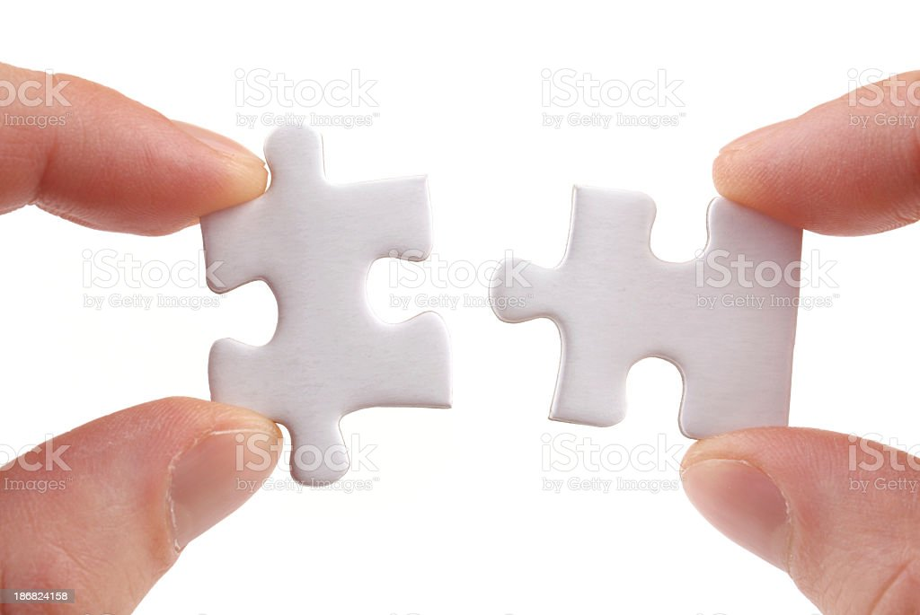 Two white jigsaw puzzle pieces being slotted together royalty-free stock photo