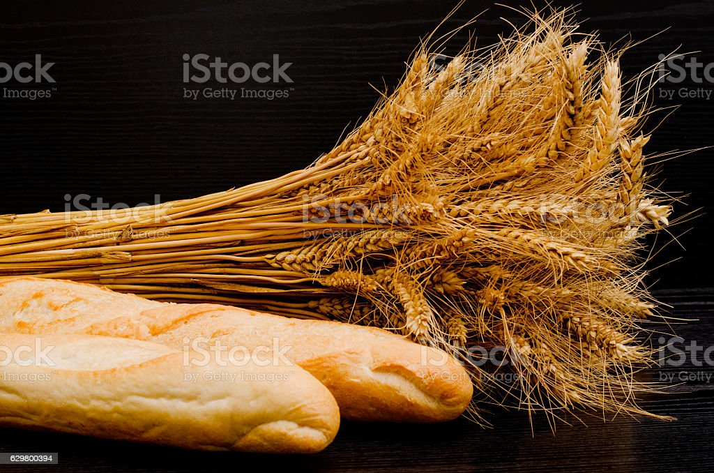 Two white loaf and a sheaf on a black background stock photo