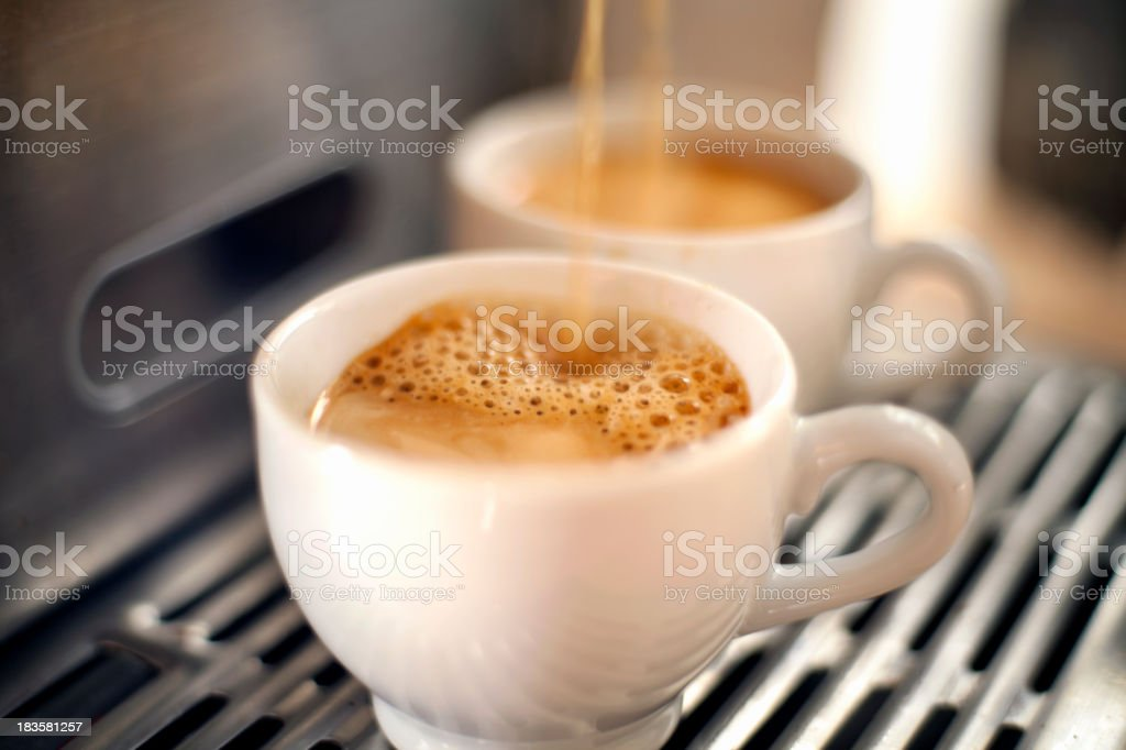 Two white mugs being filled with espresso royalty-free stock photo