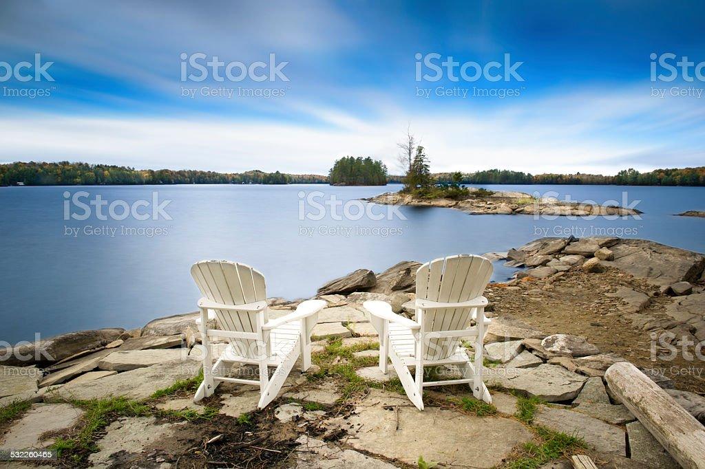 Two white Muskoka chairs facing the lake stock photo