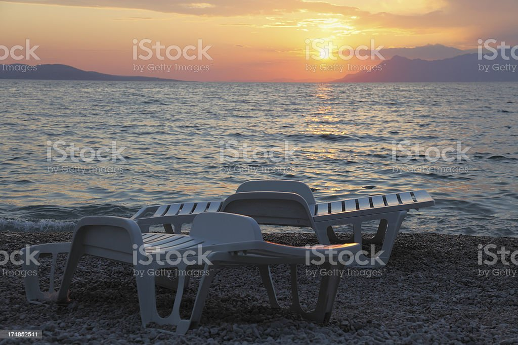 two white plastic sunbed against mediterranean ocean sunset royalty-free stock photo