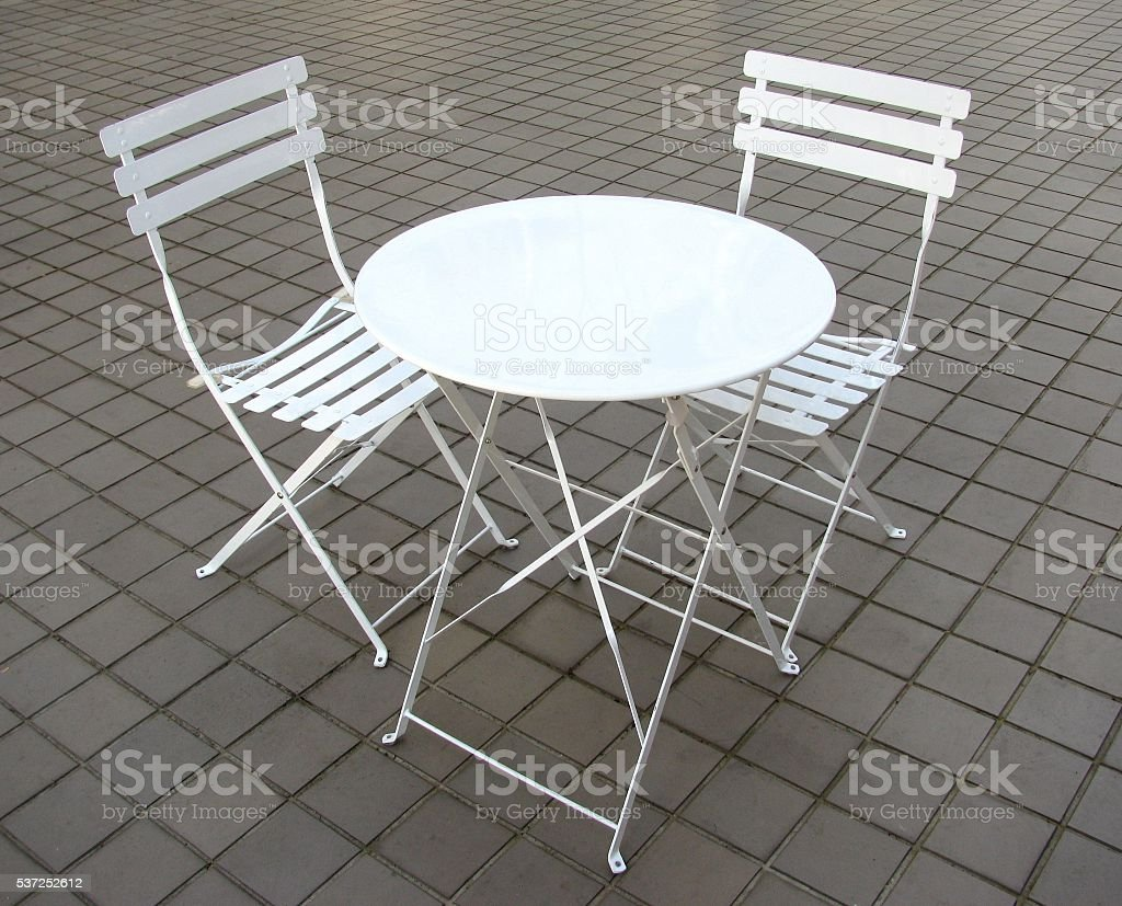 Two white small chairs and table stock photo