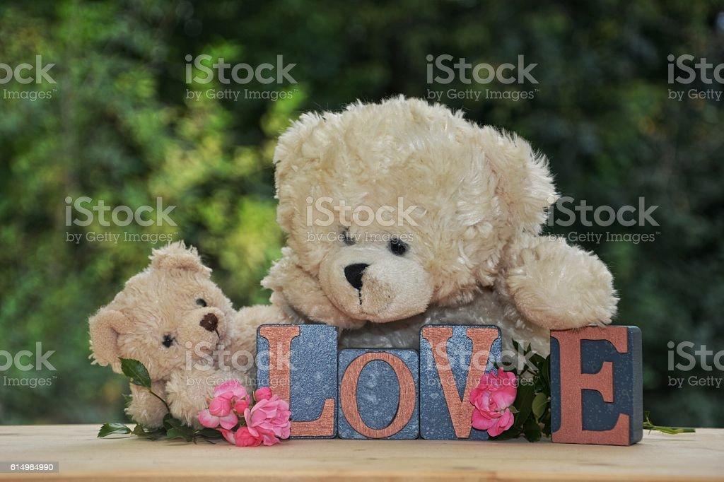 Two white teddy bear lies on Love stones stock photo