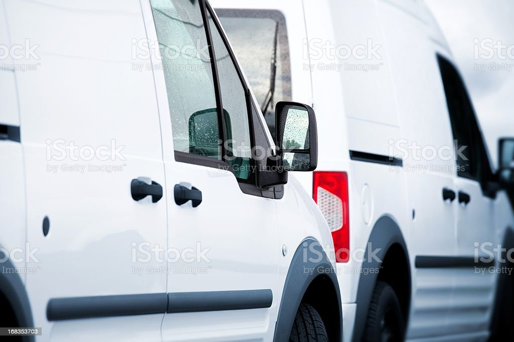 Two white vans in a parking lot stock photo