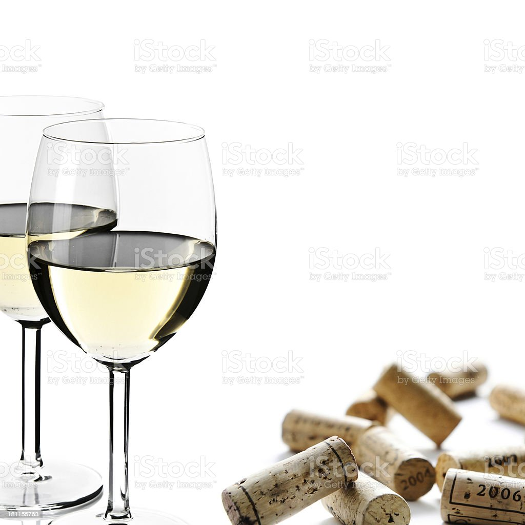 Two white wine glasses with group of scattered corks, isolated royalty-free stock photo