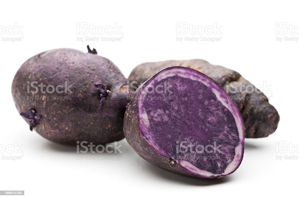 Two whole and one sliced purple potato stock photo