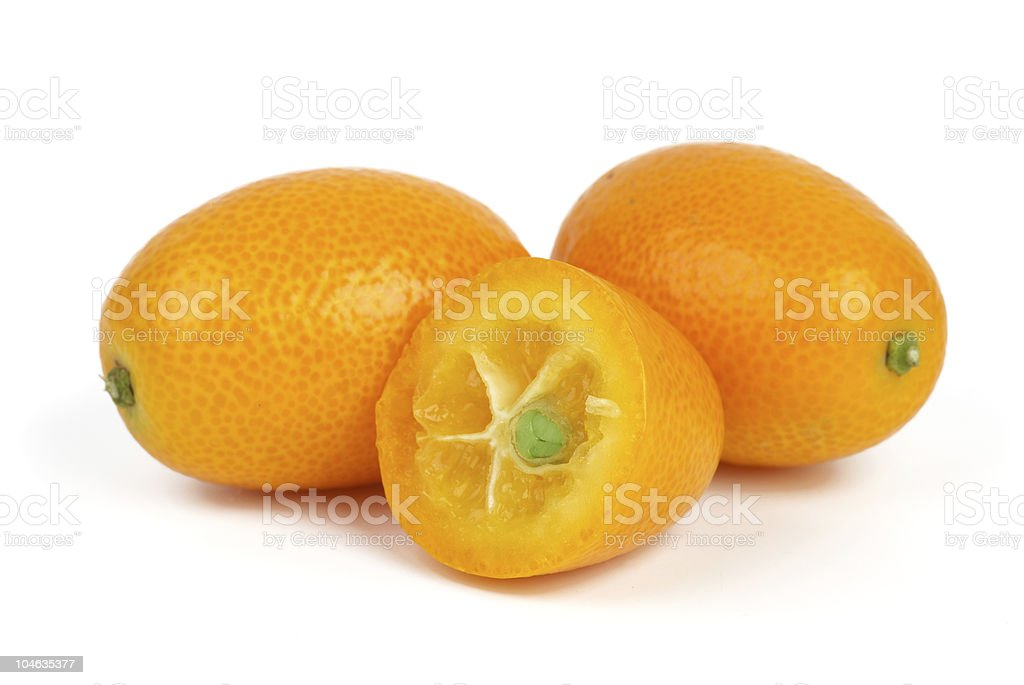 Two whole and sliced kumquat fruits royalty-free stock photo