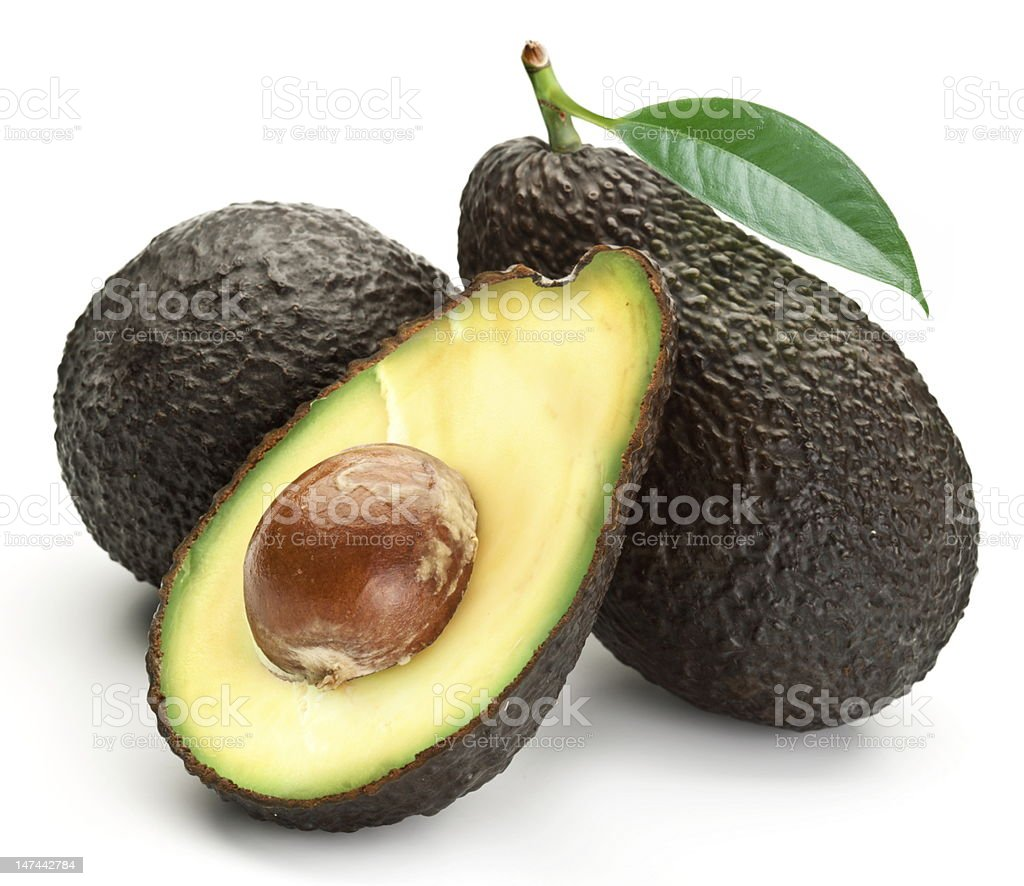 Two whole avocados with leaves and one half stock photo