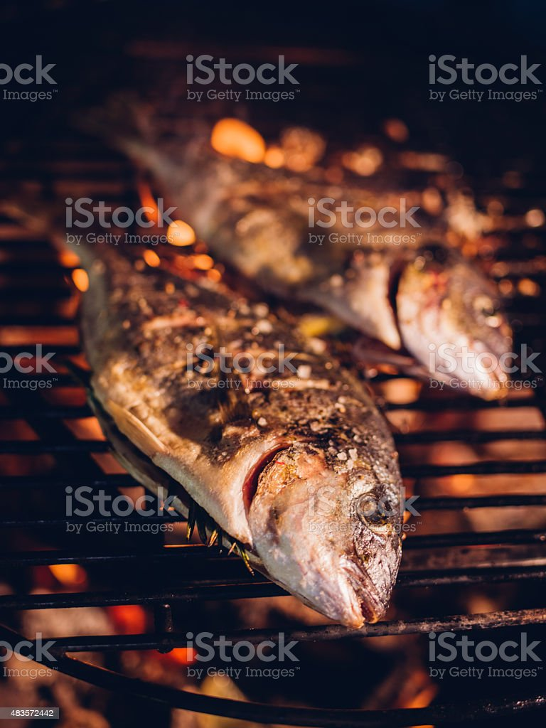 Two whole fish grilling on a glowing night barbecue stock photo