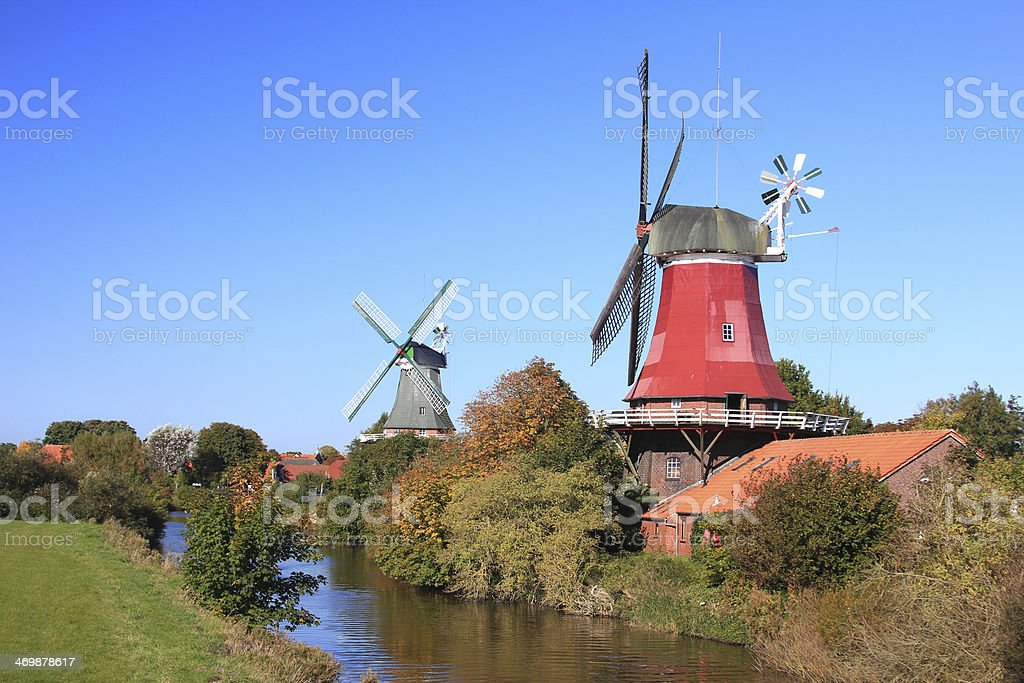 Two windmills overlooking a creek in East Frisia, Germany stock photo