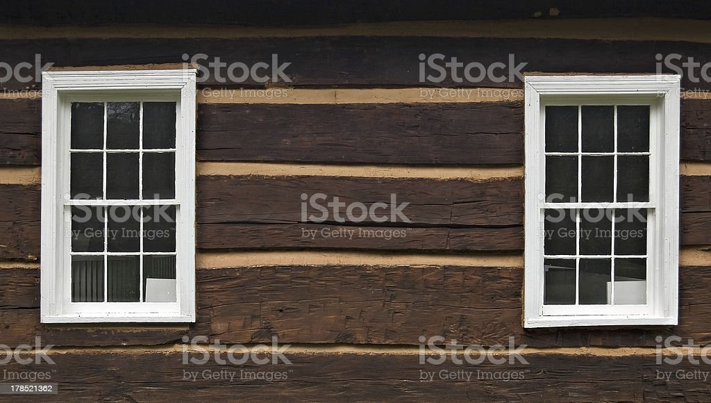 Two windows of a log cabin stock photo