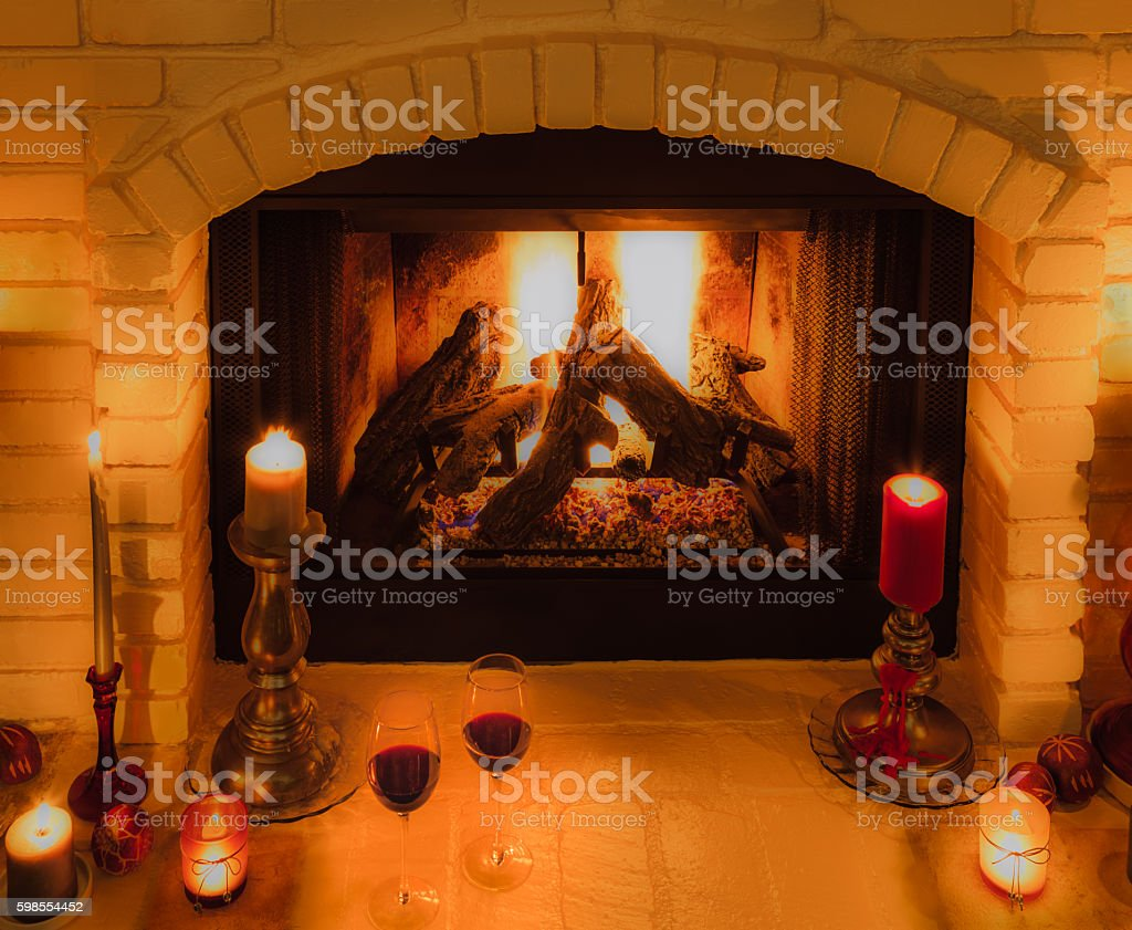 Two wine glasses sit among candles on fireplace hearth(P) stock photo