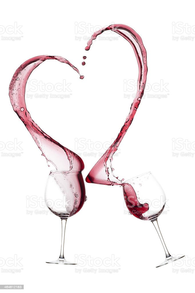 Two wine glasses with pink wine spilling out to form a heart stock photo