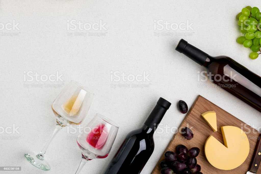 Two wine glasses with red and white wine,bottles of red wine and white wine, cheese on white background. Horizontal view from the top stock photo