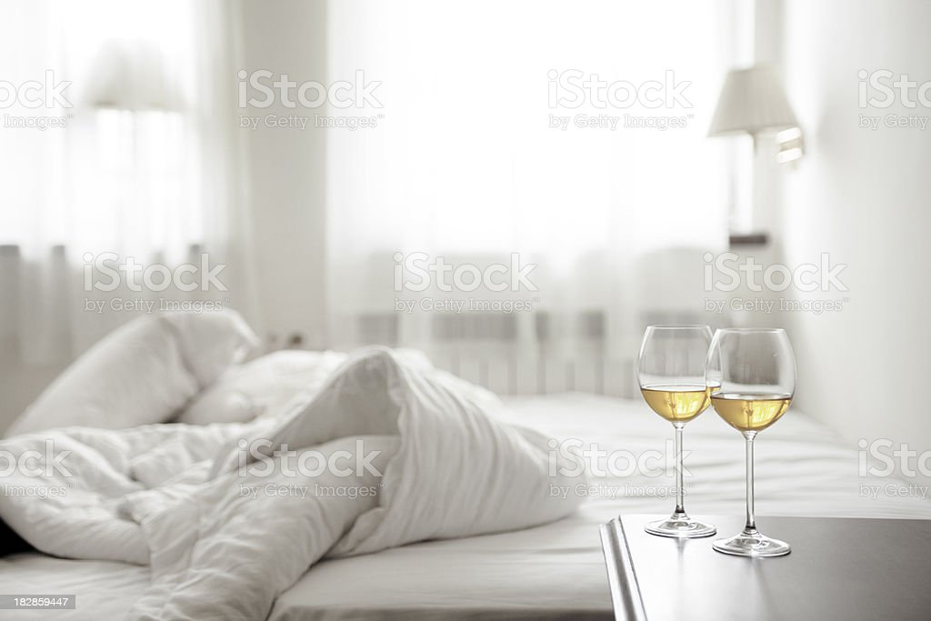 Two wineglasses and wrinkled bedding royalty-free stock photo